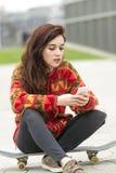 Молодая женщина битника сидя на скейтборде с телефоном стоковое фото