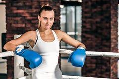 Молодая женщина боксера стоя на кольце и отдыхать Стоковое фото RF