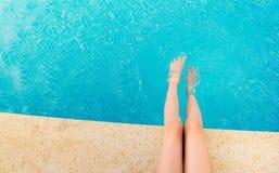Молодая женщина брызгая ноги в бассейне Стоковое Изображение