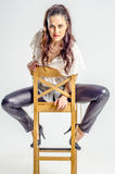 Молодая женщина брюнет в белой рубашке представляя на стуле агрессивно Стоковое фото RF
