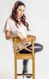 Молодая женщина брюнет в белой рубашке представляя на стуле агрессивно Стоковая Фотография RF