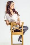 Молодая женщина брюнет в белой рубашке представляя на стуле агрессивно Стоковые Фото
