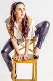 Молодая женщина брюнет в белой рубашке представляя на стуле агрессивно стоковое изображение rf