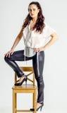 Молодая женщина брюнет в белой рубашке представляя на стуле агрессивно стоковые фотографии rf
