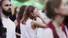 Молодая женщина брюнет в белых танцах рубашки в людях толпится на под открытым небом концерте акции видеоматериалы