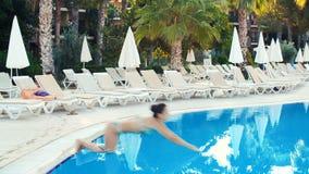 Молодая женщина брюнет в бикини скачет в бассейн на солнечный летний день сток-видео