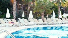 Молодая женщина брюнет в бикини скачет в бассейн на солнечный летний день движение медленное видеоматериал