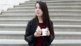 Молодая женщина брюнет в городе есть сандвич и выпивать акции видеоматериалы