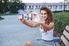 Молодая женщина брюнет в парке делая selfie Стоковые Фото