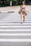 Молодая женщина брюнет в платье пересекая улицу с кофейной чашкой Стоковые Фото