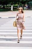 Молодая женщина брюнет в платье пересекая улицу с кофейной чашкой Стоковая Фотография