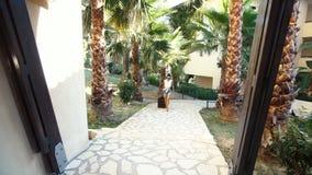 Молодая женщина брюнет в шортах, солнечных очках и пятках приходит с чемоданом между пальмами в гостинице Каникулы акции видеоматериалы