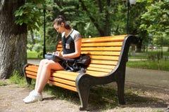 Молодая женщина брюнет изучая в парке Стоковая Фотография