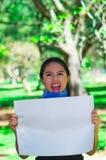 Молодая женщина брюнет нося голубой bandana вокруг шеи, держа белый плакат chanting outdoors смотреть на камеру, активист Стоковые Изображения RF
