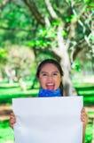 Молодая женщина брюнет нося голубой bandana вокруг шеи, держа белый плакат chanting outdoors смотреть на камеру, активист Стоковая Фотография