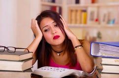 Молодая женщина брюнет нося розовую верхнюю часть сидя столом с стогом книг помещенных на ей, отдыхая головы на руку, утомляла Стоковая Фотография