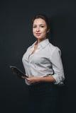 Молодая женщина брюнет представляя против черноты Стоковые Фото