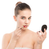 Молодая женщина брюнет при совершенная чистая сторона прикладывая губную помаду используя зеркало белизна изолированная веником Стоковые Изображения