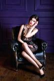 Молодая женщина брюнет сидя на кресле и смотря на камере стоковое изображение rf