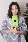Молодая женщина близко украсила рождественскую елку стоковое изображение rf