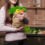 Молодая женщина варя в кухне дома Девушка в кухне держит бумажную сумку с свежими овощами и зелеными цветами Стоковое Изображение RF