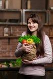 Молодая женщина варя в кухне дома Девушка в кухне держит бумажную сумку с свежими овощами и зелеными цветами Стоковые Изображения