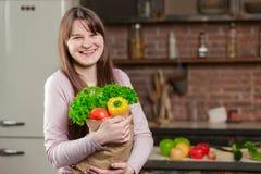 Молодая женщина варя в кухне дома Девушка в кухне держит бумажную сумку с свежими овощами и зелеными цветами Стоковые Фото