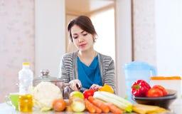 Молодая женщина варя еду veggie стоковые изображения rf