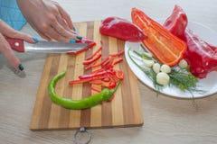 Молодая женщина варя здоровую еду в кухне Варящ здоровую еду дома Стоковая Фотография RF