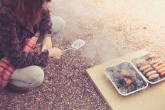 Молодая женщина варя на барбекю стоковые фотографии rf