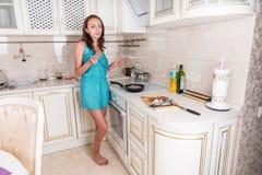 Молодая женщина варя на верхней части плиты в кухне Стоковое фото RF