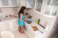 Молодая женщина варя на верхней части плиты в кухне Стоковые Изображения RF