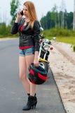 Молодая женщина велосипедиста говоря на мобильном телефоне пока держащ шлем мотоцикла Стоковые Изображения RF