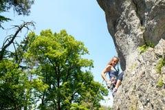 Молодая женщина взбираясь стена утеса Стоковая Фотография RF