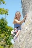 Молодая женщина взбираясь стена утеса Стоковое Изображение RF