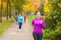 Молодая женщина 4 вне бежать совместно в парке Стоковые Изображения RF