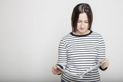 Молодая женщина внимательно читая кассету в их руках на b Стоковые Изображения