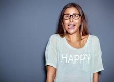 Молодая женщина вставляя вне ее язык на камере Стоковые Изображения RF