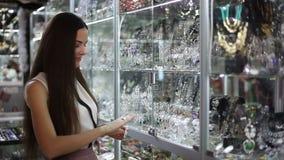 Молодая женщина выбирает ювелирные изделия в магазине сток-видео