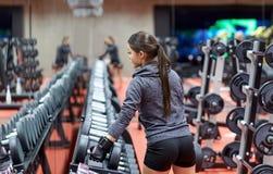 Молодая женщина выбирая гантели в спортзале Стоковое Фото