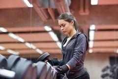 Молодая женщина выбирая гантели в спортзале Стоковое Изображение RF