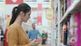 Молодая женщина выбирая деталь на полках в магазине, хочет купить химикаты домочадца 4K видеоматериал