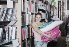 Молодая женщина выбирая одеяло и подушку Стоковое Изображение RF