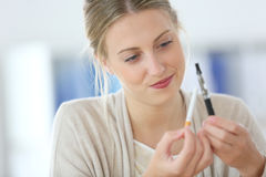 Молодая женщина выбирая для электронной сигареты Стоковое Изображение