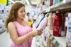 Молодая женщина выбирая cleanser в магазине Стоковое Изображение