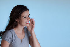 Молодая женщина вызывая кто-то с рукой рядом с ртом Стоковые Изображения