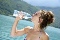 Молодая женщина выпивает бутылку воды к пляжу Стоковое Фото