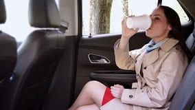 Молодая женщина выпивает кофе на заднем сиденье автомобиля сток-видео