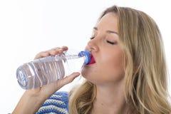 Молодая женщина выпивая от бутылки воды при закрытые глаза Стоковое Изображение RF