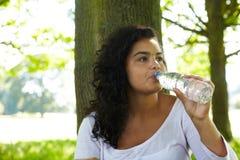 Молодая женщина выпивая от бутылки воды Стоковые Изображения